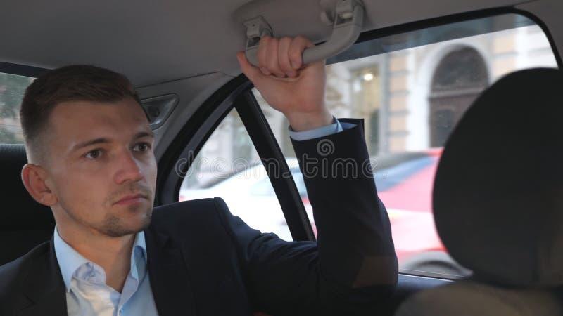 Jeune homme d'affaires s'asseyant sur la banquette arrière dans la voiture et parler L'homme s'assied sur un siège au fond d'auto photo stock