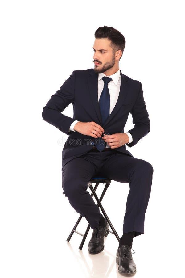 Jeune homme d'affaires s'asseyant sur la chaise et boutonnant son costume photos stock