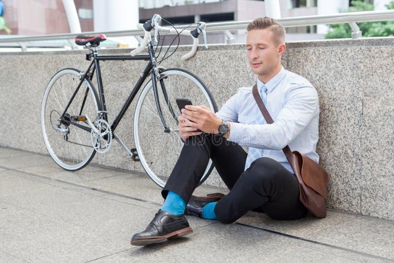 Jeune homme d'affaires s'asseyant sur le plancher avec la bicyclette utilisant le smartphone prenant un repos et détendant sur la photos libres de droits