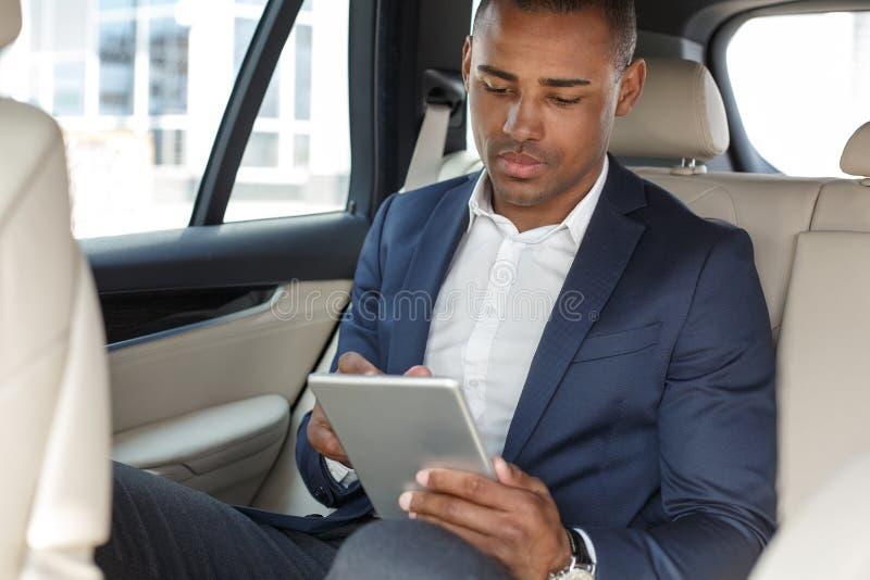 Jeune homme d'affaires s'asseyant sur le siège arrière dans la voiture passant en revue le comprimé numérique concentré photos stock