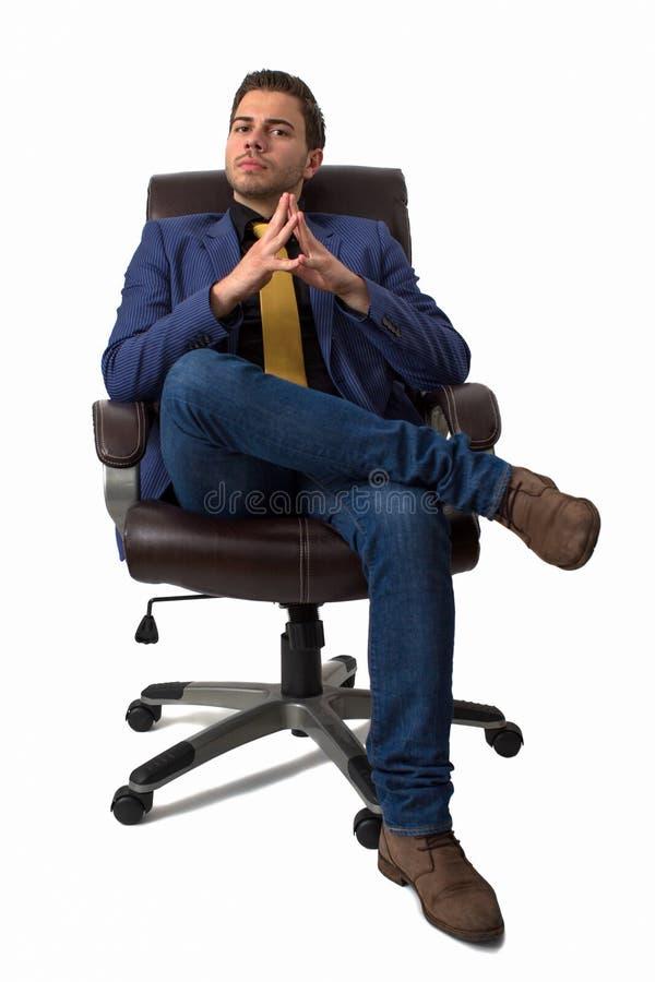 Jeune homme d'affaires s'asseyant sur une présidence photographie stock