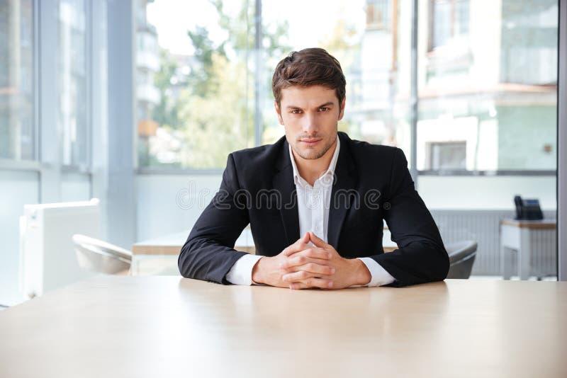 Jeune homme d'affaires sûr s'asseyant à la table dans le bureau photos libres de droits