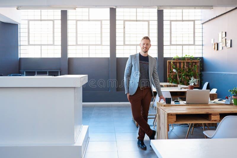 Jeune homme d'affaires sûr seul se tenant dans un bureau moderne photo stock