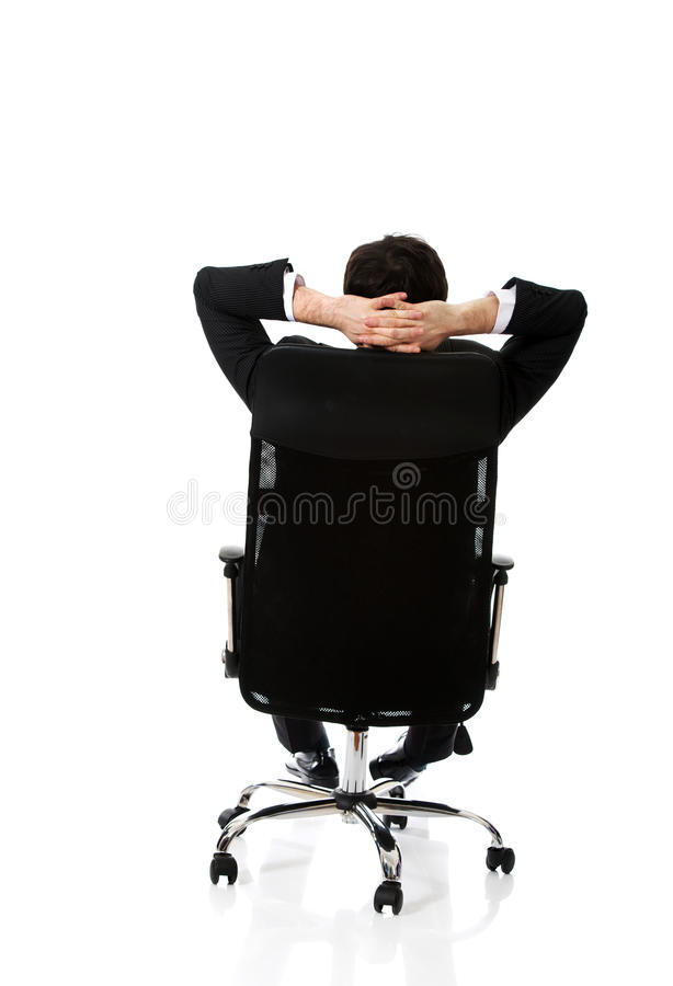Jeune homme d'affaires sesting sur une chaise photographie stock libre de droits
