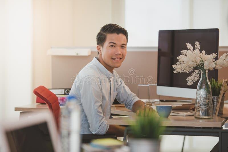 Jeune homme d'affaires souriant tout en se reposant à son lieu de travail dans le bureau photo libre de droits