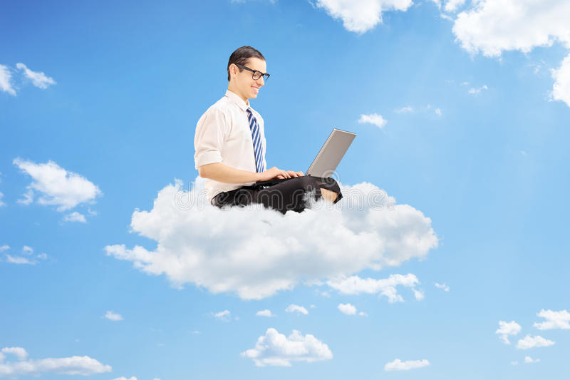 Jeune homme d'affaires sur des nuages travaillant sur un ordinateur portable photo stock