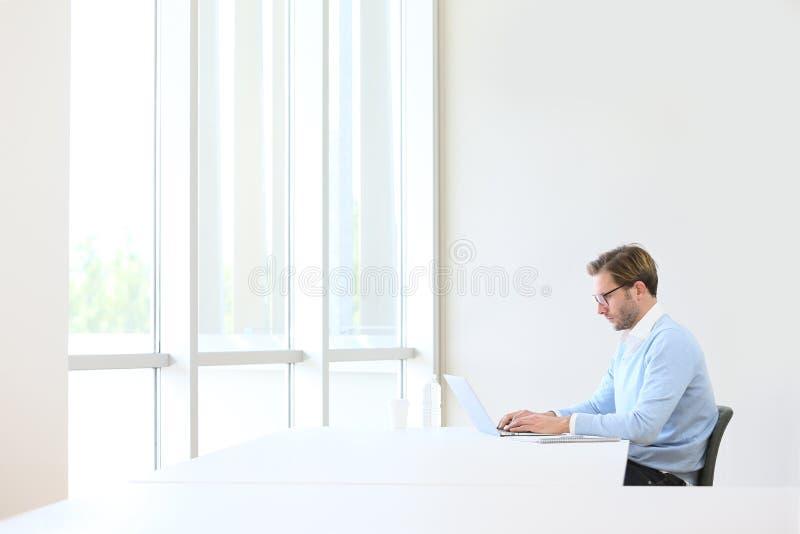 Jeune homme d'affaires sur l'ordinateur portable d'isolement photographie stock