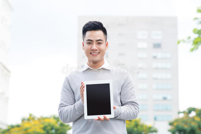 Jeune homme d'affaires tenant et montrant l'écran du comprimé photos stock