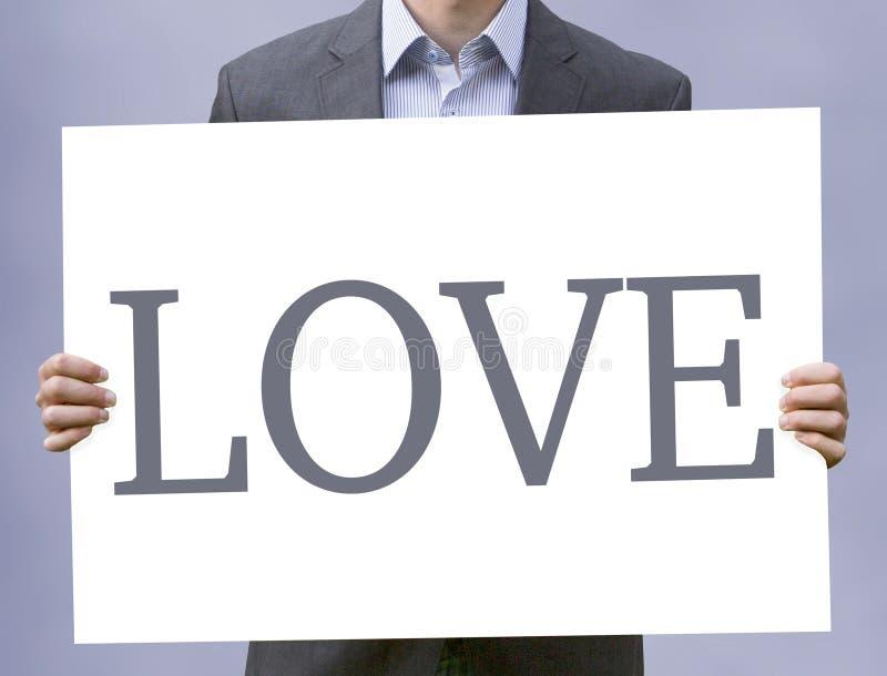 Jeune homme d'affaires tenant le signe avec l'amour de mot photo stock