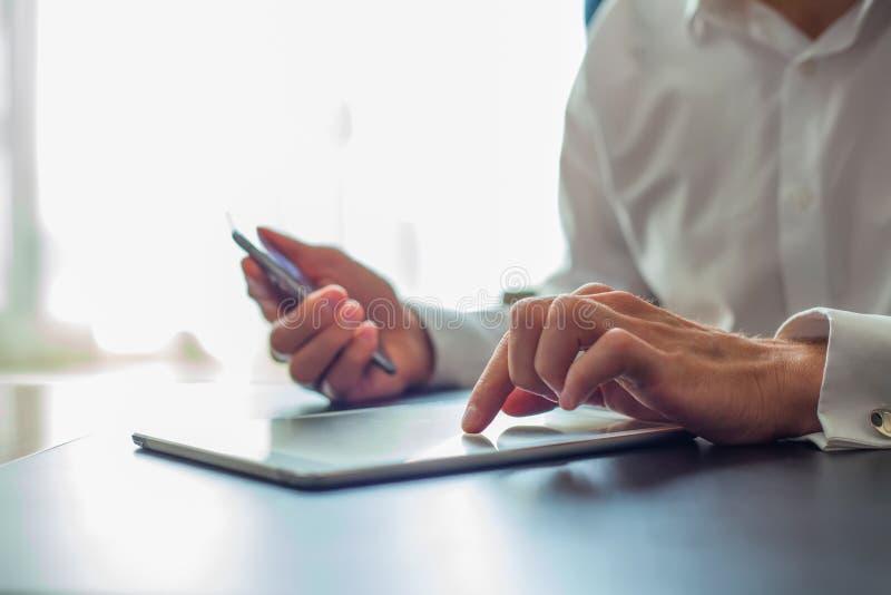 Jeune homme d'affaires travaillant avec les dispositifs modernes, la tablette numérique et le téléphone portable photos stock