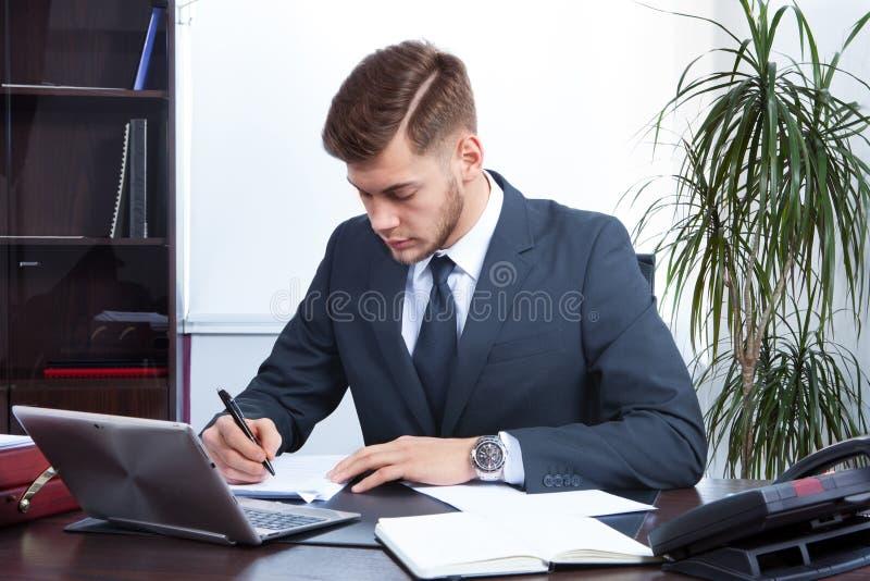 Jeune homme d'affaires travaillant dans le bureau images libres de droits