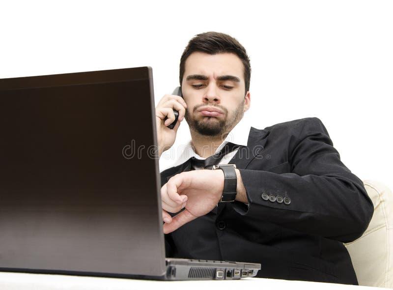 Jeune homme d'affaires travaillant des heures supplémentaires le foyer sur la montre photographie stock
