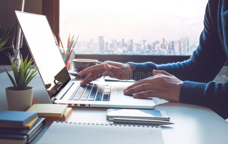 Jeune homme d'affaires travaillant sur l'ordinateur portable dans le bureau avec la vue de ville de fenêtre photographie stock libre de droits
