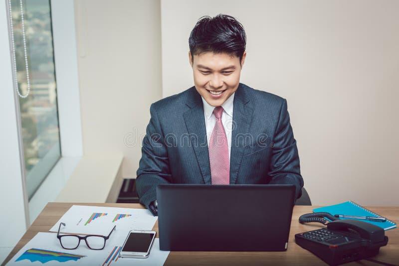 Jeune homme d'affaires travaillant sur l'ordinateur portatif photographie stock