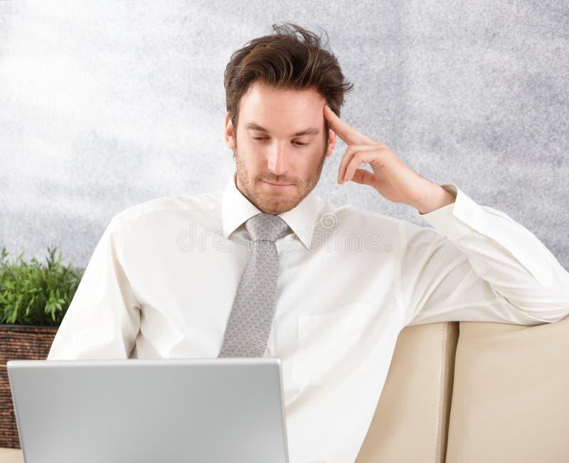 Jeune homme d'affaires travaillant sur l'ordinateur portatif photos stock