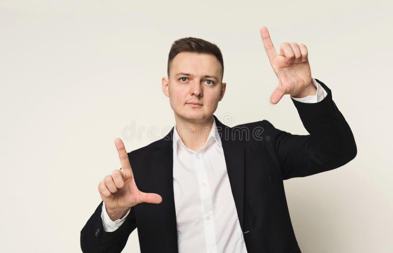 Jeune homme d'affaires utilisant l'écran virtuel pour le travail photographie stock