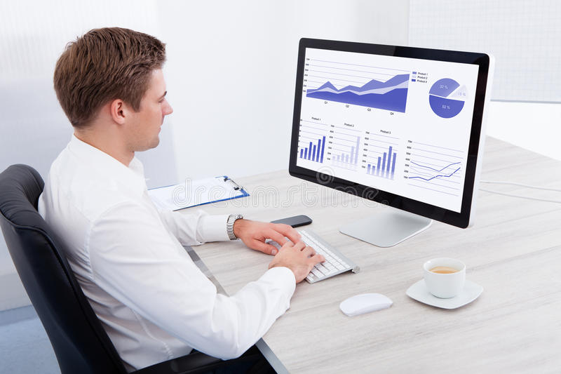 Jeune homme d'affaires utilisant l'ordinateur au bureau image libre de droits