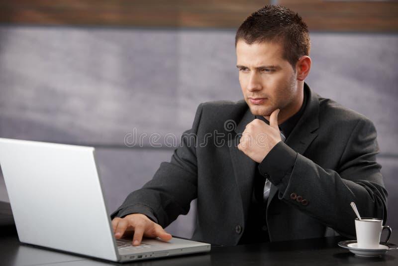 Jeune homme d'affaires utilisant l'ordinateur portatif dans le bureau images libres de droits