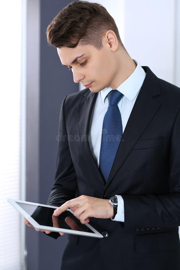 Jeune homme d'affaires utilisant la tablette tout en se tenant directement dans le bureau Concept d'affaires images libres de droits