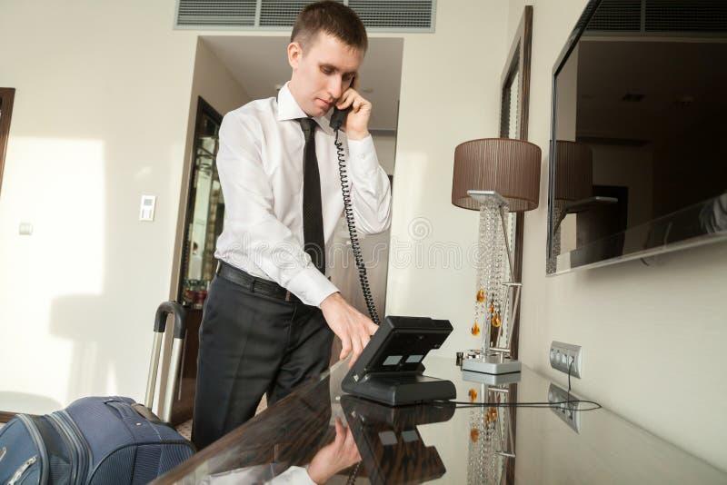 Jeune homme d'affaires utilisant le téléphone dans la chambre d'hôtel image libre de droits