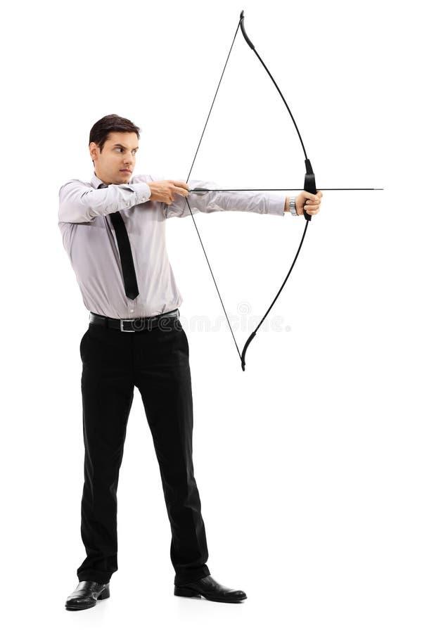 Jeune homme d'affaires visant avec un tir à l'arc images stock