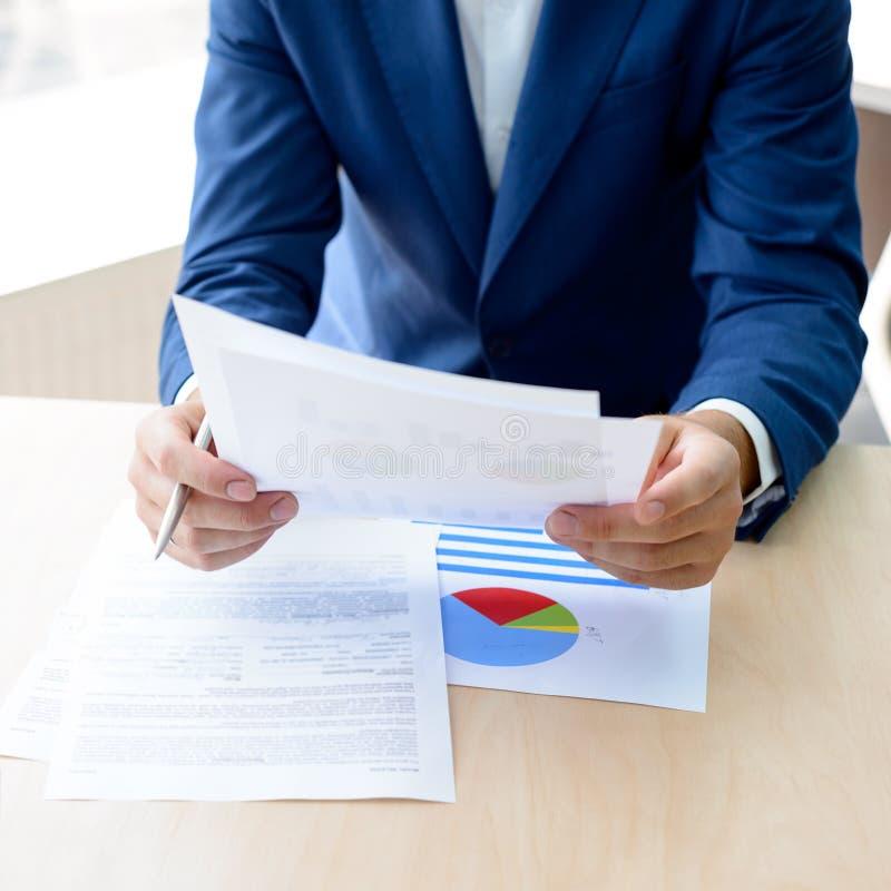 Jeune homme d'affaires Working avec la documentation financière dans le bureau moderne Concept d'affaires photo libre de droits