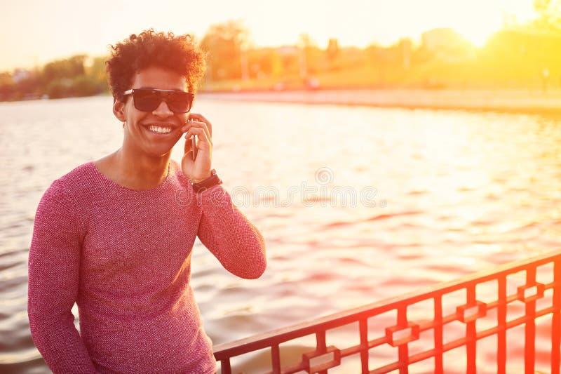 Jeune homme d'africain noir avec le téléphone portable au-dessus de la lumière du soleil image libre de droits