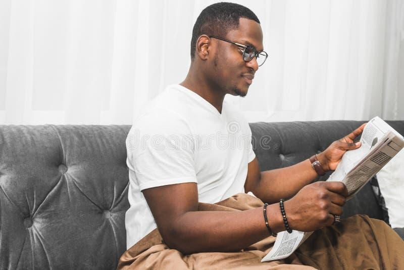 Jeune homme d'Afro-américain, couvert de couverture lisant un journal à la maison photos libres de droits