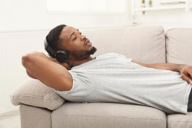 Jeune homme d'afro-américain dans des écouteurs à la maison photo stock