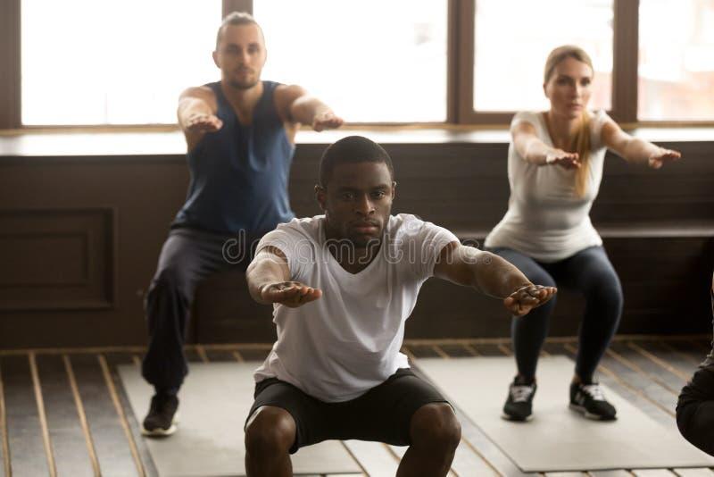 Jeune homme d'afro-américain faisant des exercices accroupis aux fitnes de groupe photos libres de droits