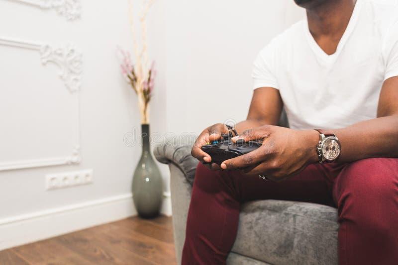 Jeune homme d'Afro-américain jouant une console de jeu à la maison photos stock