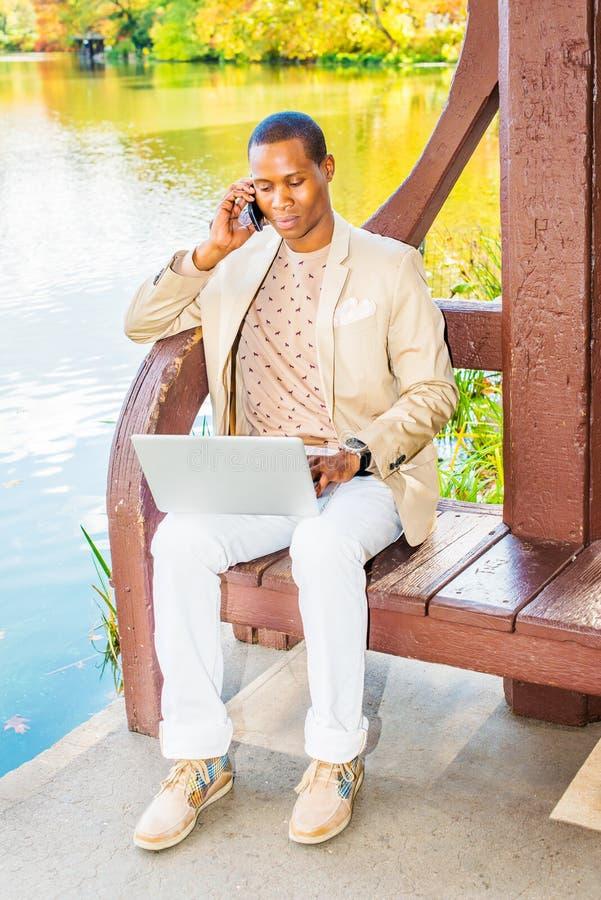 Jeune homme d'Afro-américain parlant au téléphone portable, travaillant au recouvrement image stock