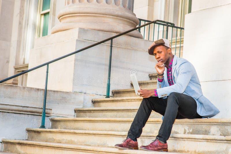 Jeune homme d'Afro-américain travaillant sur l'ordinateur portable dehors dedans photos stock