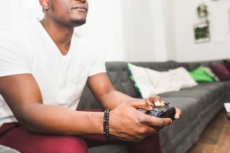 Jeune homme d'Afro-am?ricain jouant une console de jeu ? la maison photos stock