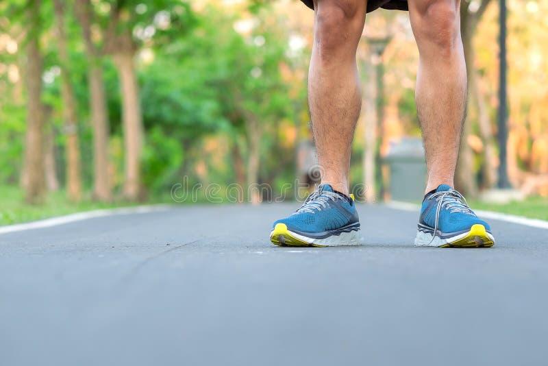 Jeune homme d'athlète avec les chaussures de course en parc extérieur, coureur masculin prêt pour pulser sur la route dehors, mar images stock