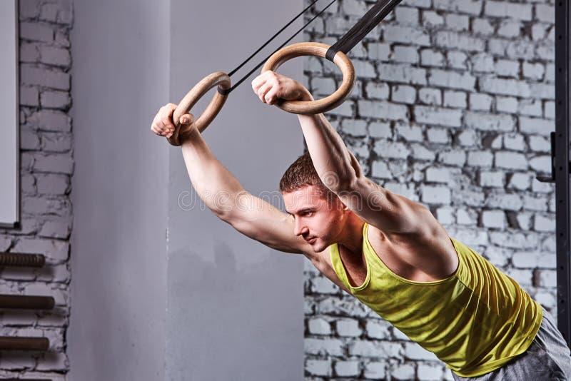 Jeune homme d'athlète dans le sportwear tirant vers le haut sur les anneaux gymnastiques contre le mur de briques dans le gymnase images stock