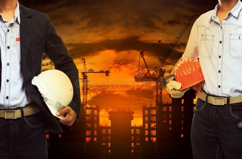 Jeune homme d'ingénieur se tenant avec le casque de sécurité contre le bâtiment photo stock