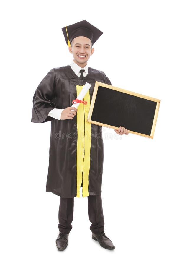 Jeune homme d'obtention du diplôme tenant le certificat et conseil noir vide image libre de droits