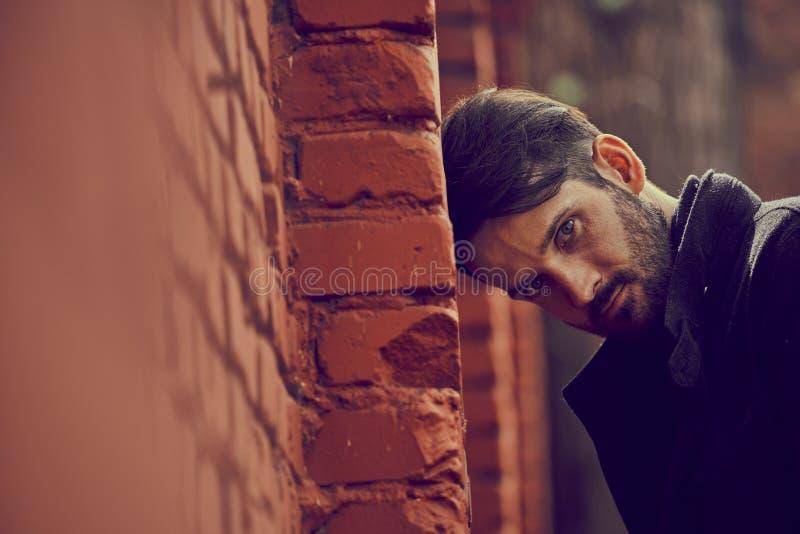 Jeune homme d?prim? frustrant pr?s du mur de briques semblant f?ch? Portrait dramatique modifi? la tonalit? triste de plan rappro images libres de droits