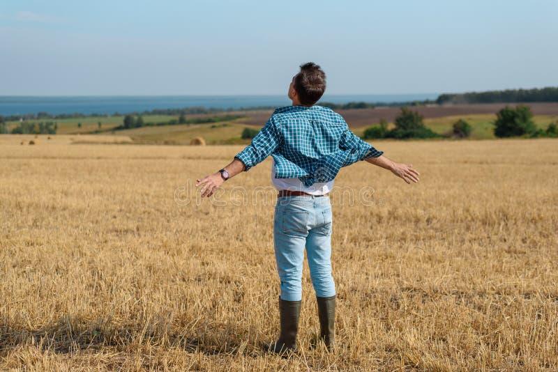 Jeune homme dans des jeans, chemise, bottes en caoutchouc dans le domaine avec ses mains ouvertes, le concept de la liberté, moti photographie stock libre de droits