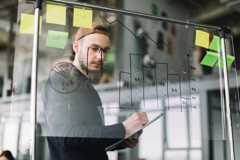 Jeune homme dans l'équipement occasionnel et le chapeau fonctionnant avec des données et des diagrammes sur le mur en verre de bu image libre de droits