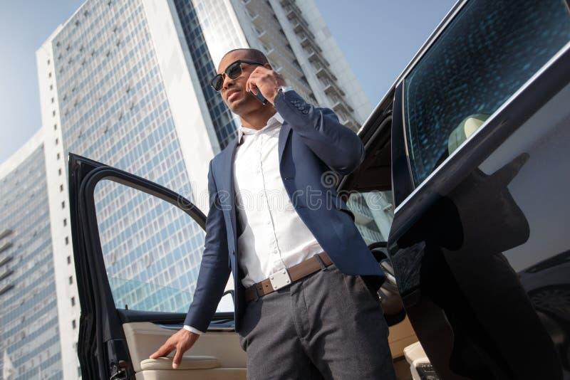 Jeune homme dans l'extinction de lunettes de soleil de la voiture invitant la vue inférieure de smartphone photographie stock