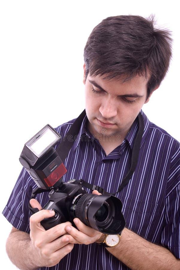 Jeune homme dans la chemise avec un appareil-photo moderne de photo de SLR images stock