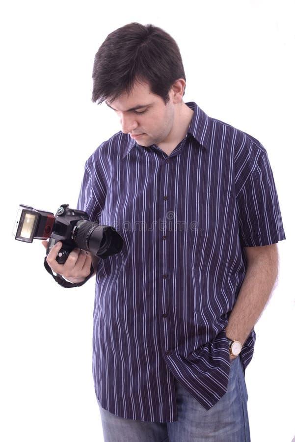 Jeune homme dans la chemise avec un appareil-photo noir de photo de SLR photo libre de droits