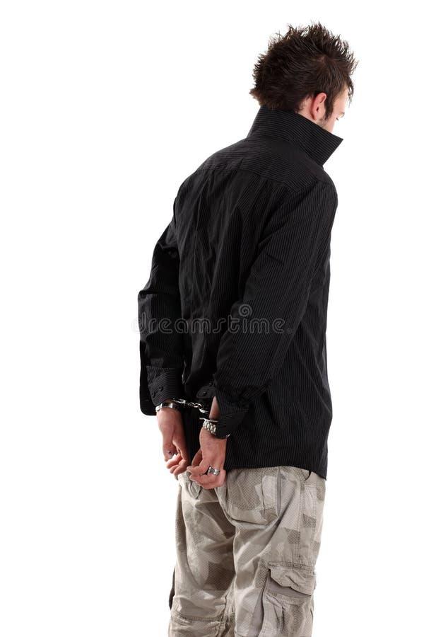 Jeune homme dans la chemise noire avec des menottes photos libres de droits