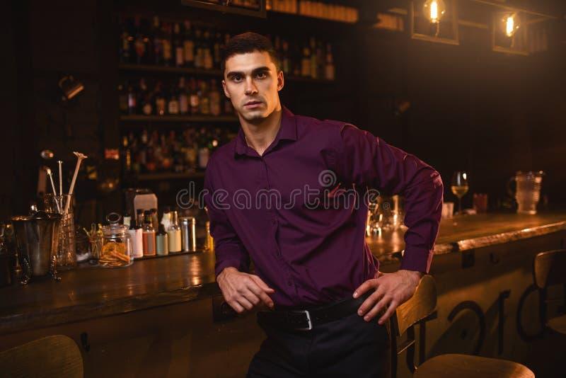 Jeune homme dans la chemise se tenant au compteur de barre photos stock