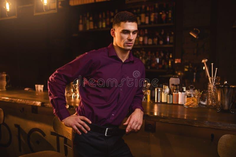 Jeune homme dans la chemise se tenant au compteur de barre photos libres de droits