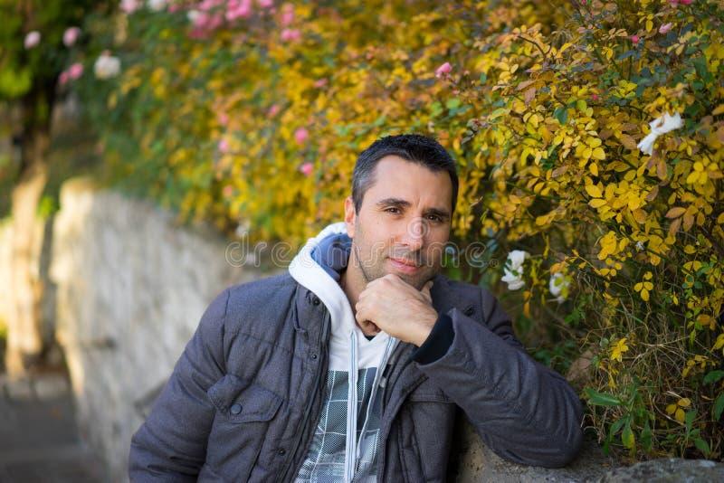 Jeune homme dans la pose de manteau photo stock