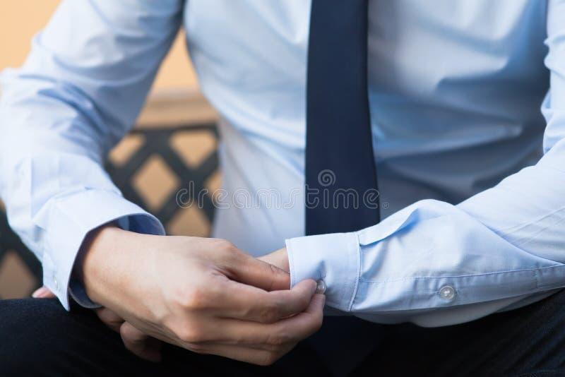 Jeune homme dans le boutonnage de chemise de local commercial que sa douille se boutonne photo stock