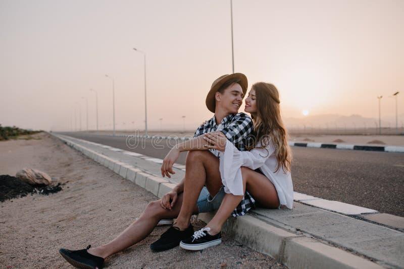 Jeune homme dans le chapeau ? la mode regardant avec amour son amie gracieuse dans la chemise blanche, tout en se reposant apr?s  photos stock